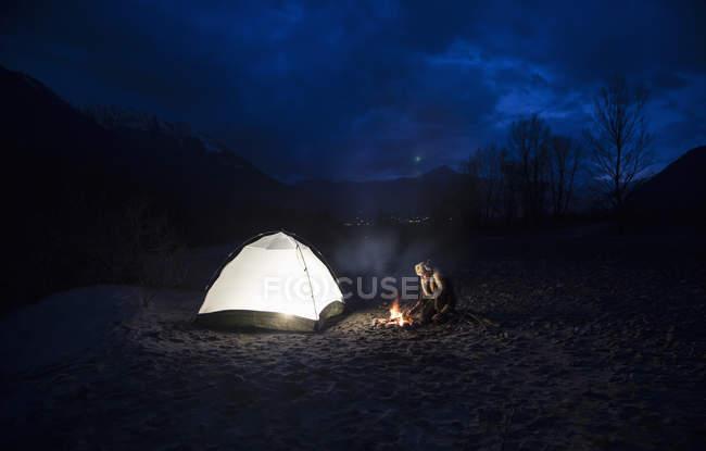 Homem pela fogueira e tenda à noite — Fotografia de Stock