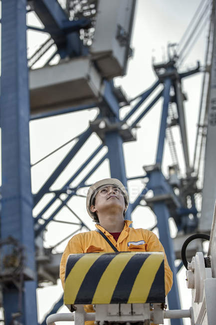 Crane driver looking up from control panel at dock — Stock Photo