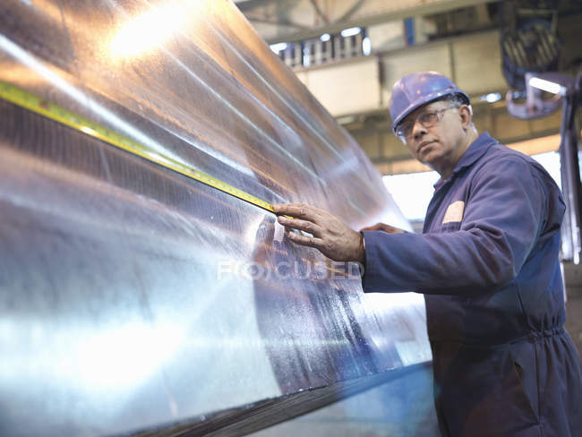 Engineer setting up specialist lathe in steel engineering factory — Stock Photo
