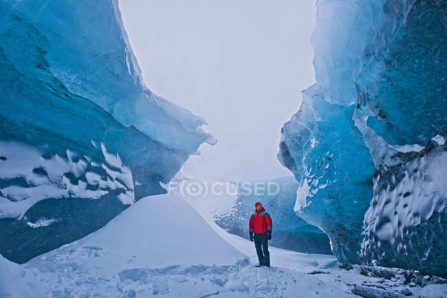 Uomo maturo in piedi accanto a pile di esplorare cristallo ghiaccio grotta di neve, Breidamerkurjokull, Vatnajokull, Islanda — Foto stock