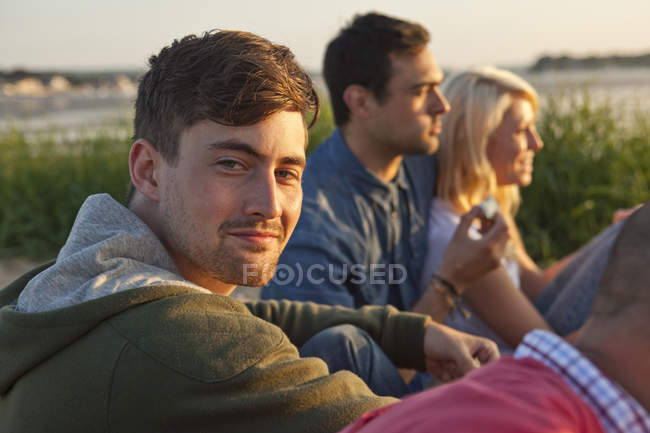 Four friends sitting on Bournemouth beach, Dorset, UK — Stock Photo