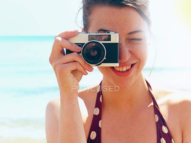Young woman using camera on beach — Stock Photo