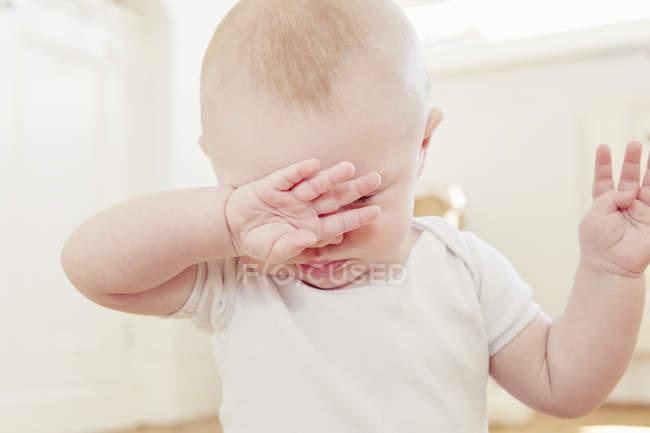 Close-up do bebé tired com os olhos da fricção da mão — Fotografia de Stock