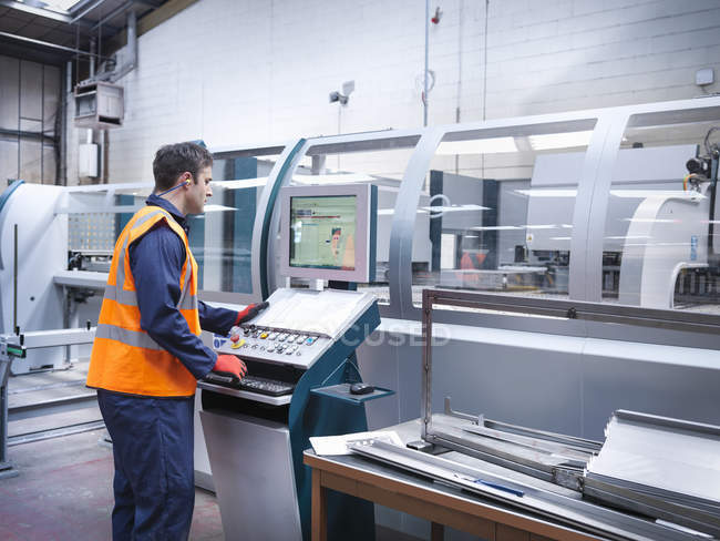 Ouvrier utilisant la machine robotique de découpage de métal dans l'usine de tôle — Photo de stock