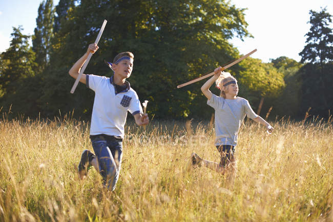 Two little boys running with bows and arrows — Stock Photo