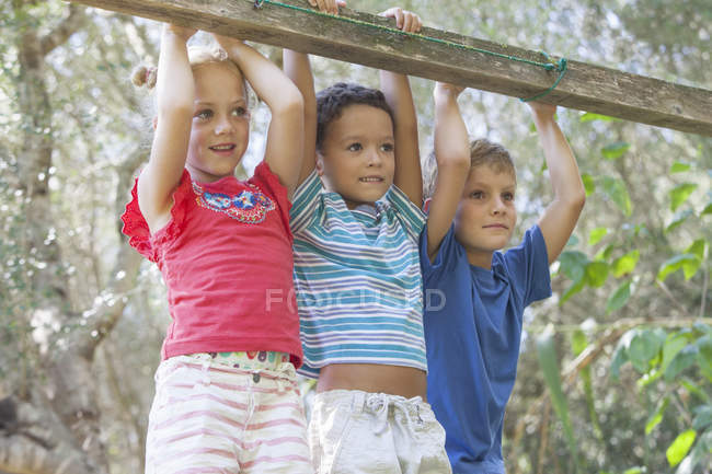 Three children looking away in garden — Stock Photo