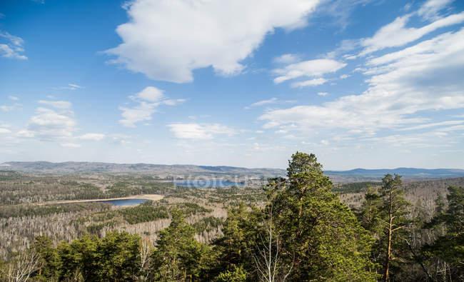 Vue sur forêt, montagnes et lac en plein soleil — Photo de stock