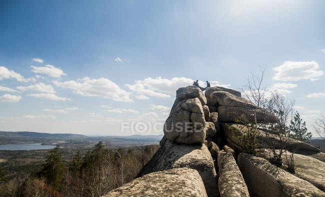 Trois randonneurs mâles au-dessus de la formation de roche avec le lac dans la distance — Photo de stock