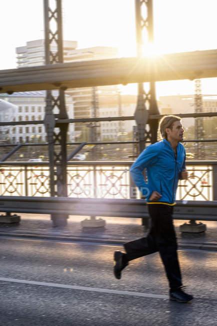 Man jogging on bridge, Munich, Bavaria, Germany — Stock Photo