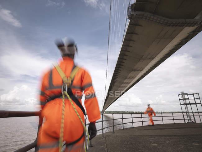 Размытый вид рабочих моста, идущих под подвесным мостом, Хамбер Бридж, Великобритания — стоковое фото