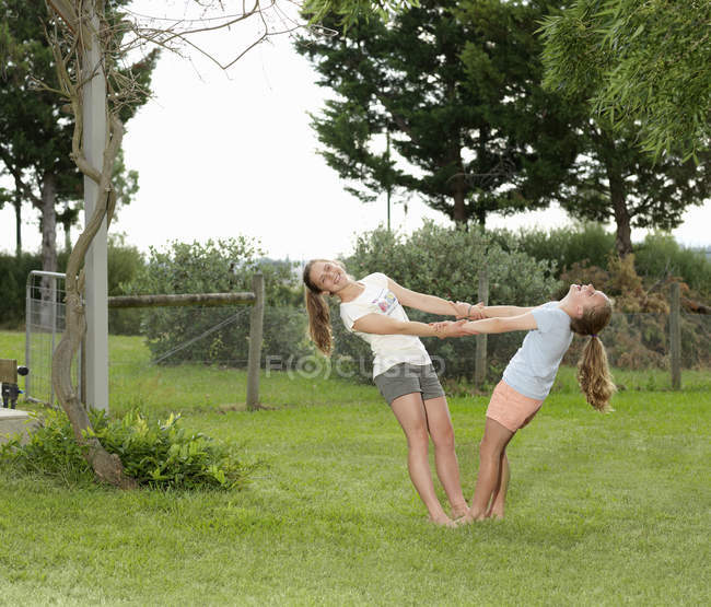Two sisters holding hands and balancing together in garden — стокове фото