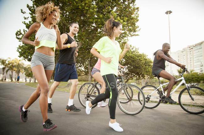 Amigos adultos haciendo el ciclo de entrenamiento y correr en el parque - foto de stock
