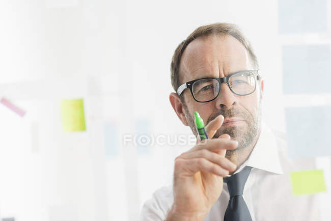 Businessman working on ideas at office glass wall — Stock Photo