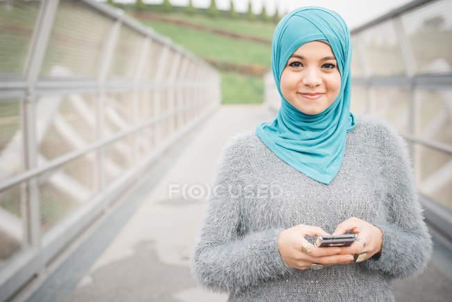 Portrait of young woman wearing turquoise hijab using smartphone on footbridge — Stock Photo