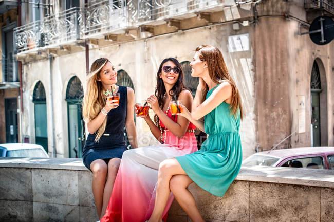 Tre giovani amiche alla moda che bevono cocktail sul marciapiede, Cagliari, Sardegna, Italia — Foto stock