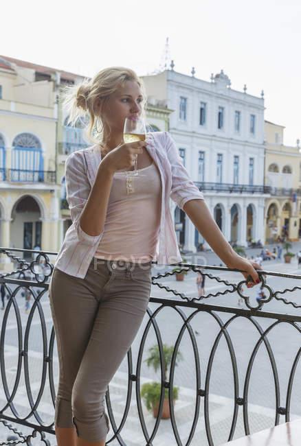 Junge Frau mit Blick vom Balkon des Restaurants im Plaza Vieja, Havanna, Kuba — Stockfoto