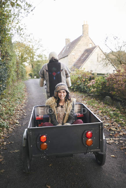 Rear view of mature hippy couple riding tricycle and trailer on rural road — Stock Photo