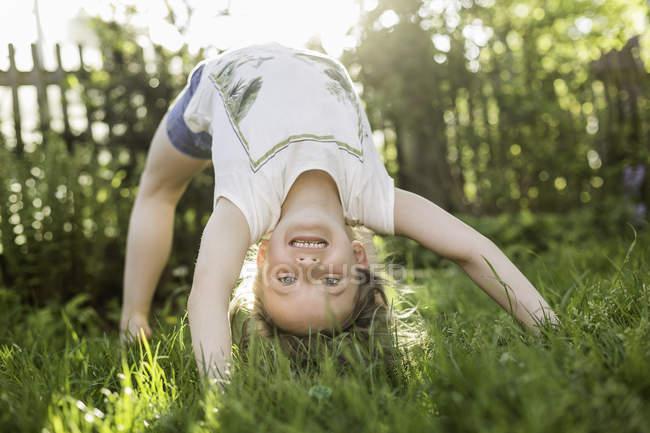 Retrato de menina dobrando-se para trás de cabeça para baixo no jardim — Fotografia de Stock