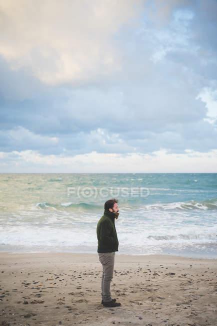 Homem adulto médio na praia tempestuosa, Sorso, Sassari, Sardenha, Itália — Fotografia de Stock