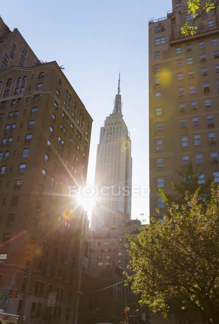 Vue ensoleillée de l'Empire State Building depuis Park Avenue, New York, États-Unis — Photo de stock