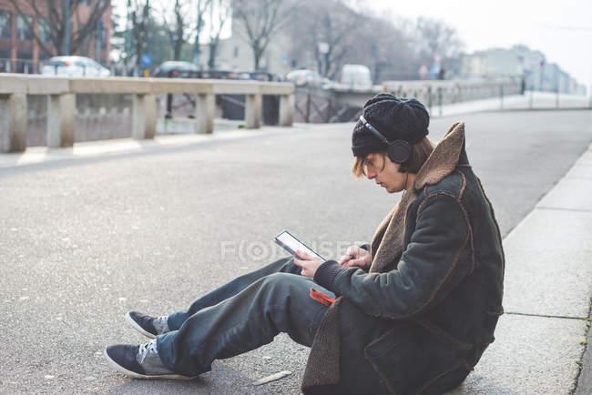 Man using digital tablet on kerb, Milan, Italy — Stock Photo