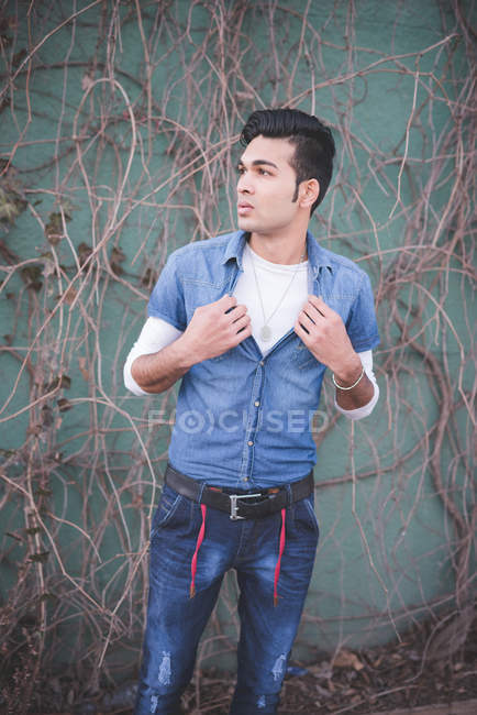 Portrait of a young man holding shirt — Stock Photo