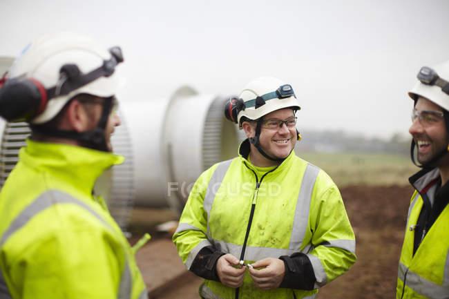 Ingénieurs en conversation sur le chantier de construction d'un parc éolien — Photo de stock