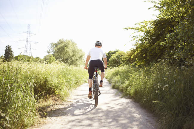 Rear view of male athlete cycling on rural path — Stock Photo