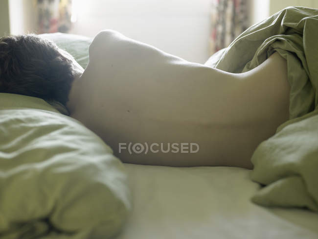 Rückansicht einer nackten jungen Frau, die im Bett liegt — Stockfoto