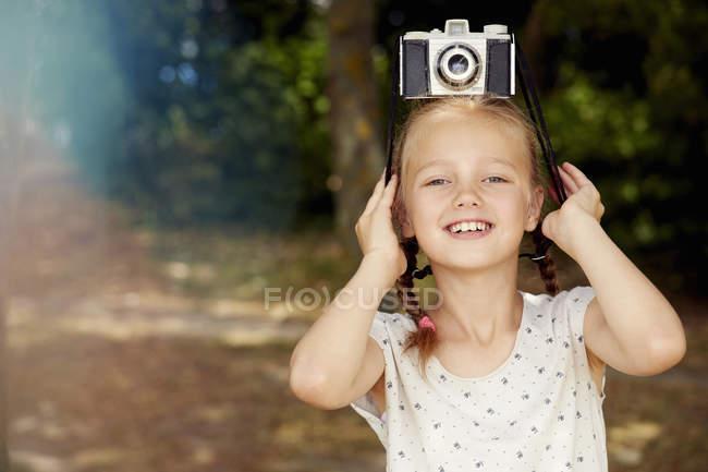 Menina com câmera de filme na cabeça olhando para a câmera e sorrindo — Fotografia de Stock