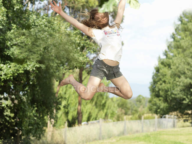 Teenage girl jumping with arms outstretched, mid-air, outdoors — Stock Photo