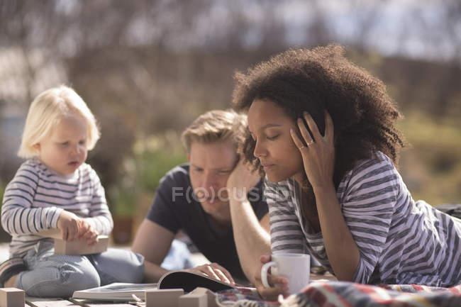Relaxando no cobertor ao ar livre no piquenique de família — Fotografia de Stock