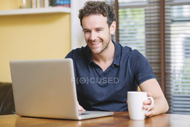 Hombre adulto medio sentado delante de la ventana sosteniendo la taza usando el ordenador portátil sonriendo - foto de stock