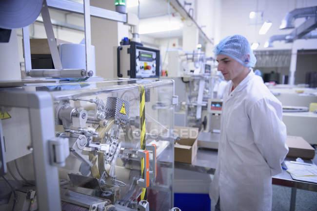 Працівник, що відвідує машину в шоколадній фабриці — стокове фото