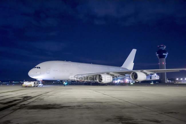 Engenheiro-chefe com aeronaves A380 em pista à noite — Fotografia de Stock