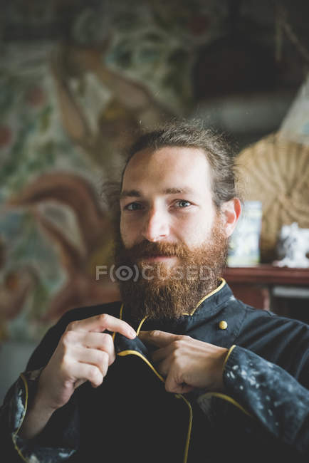 Portrait of bearded mid adult man buttoning up clay covered jacket, looking at camera smiling — Stock Photo
