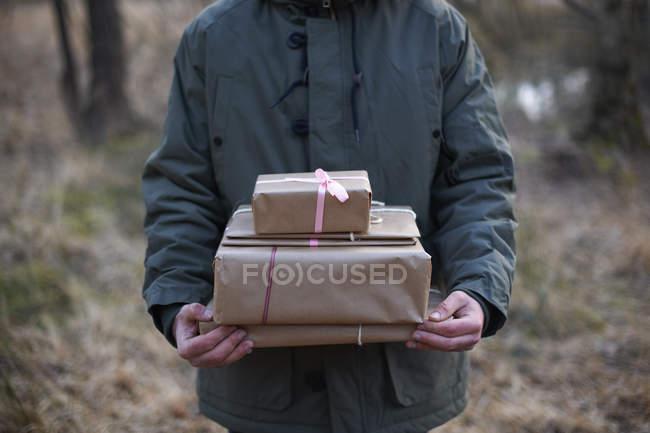 Colpo ritagliato di regali trasportati attraverso la foresta da un giovane — Foto stock