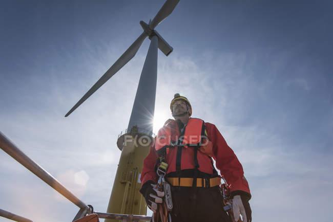 Ingegnere che si prepara a salire la turbina eolica al parco eolico offshore, vista a basso angolo — Foto stock