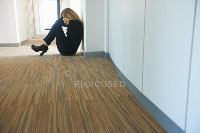 Mulher madura sentada contra a parede no corredor — Fotografia de Stock