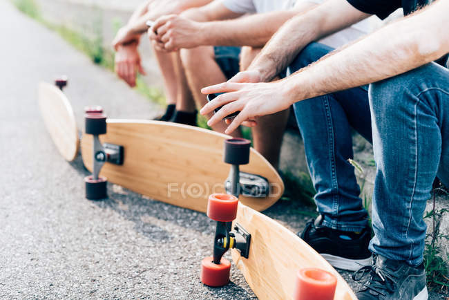 Young men sitting with skateboards — Stock Photo
