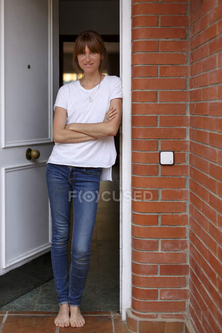 Full length view of mid adult woman leaning against door frame, arms crossed — Stock Photo