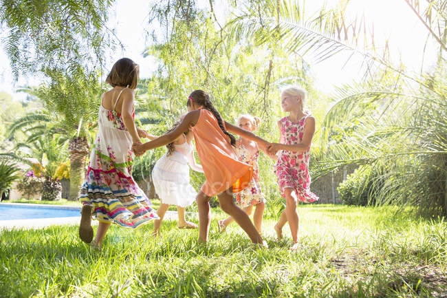 Five girls playing ring a ring a roses in garden — Stock Photo