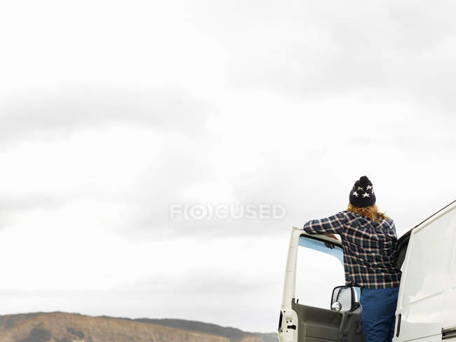 Rear view of young woman looking out from camper van — Stock Photo