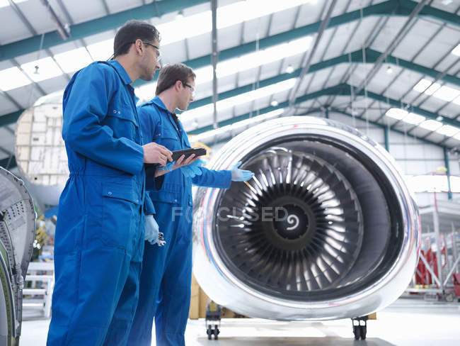 Ingenieros discutiendo motor en fábrica de mantenimiento de aeronaves - foto de stock