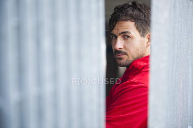 Портрет подозрительный молодой человек, глядя через плечо между столбами стоянка — стоковое фото