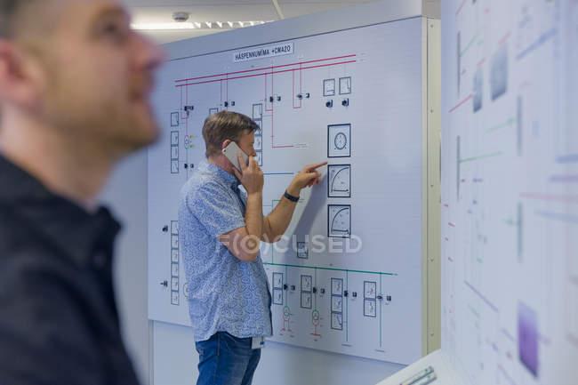 Інженер вказує на панель керування, використовуючи смартфон на геотермальній електростанції. — стокове фото