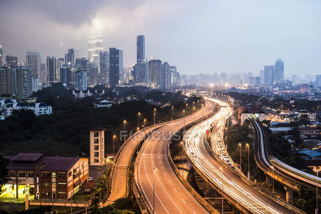 Highway with light trails and skyline at dusk, Kuala Lumpur, Malaysia — Stock Photo