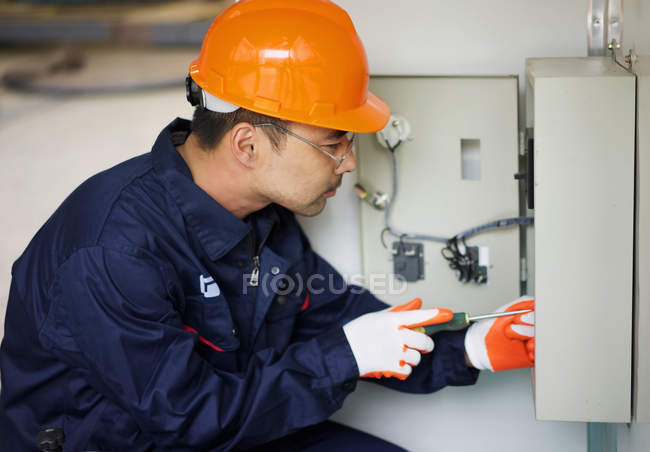 Worker working on fuse box in crane manufacturing facility, China — Stock Photo