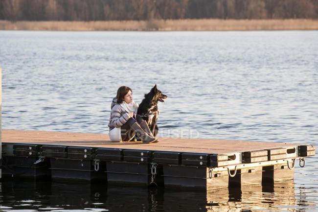 Femme adulte moyenne et son chien assis sur la jetée du lac — Photo de stock