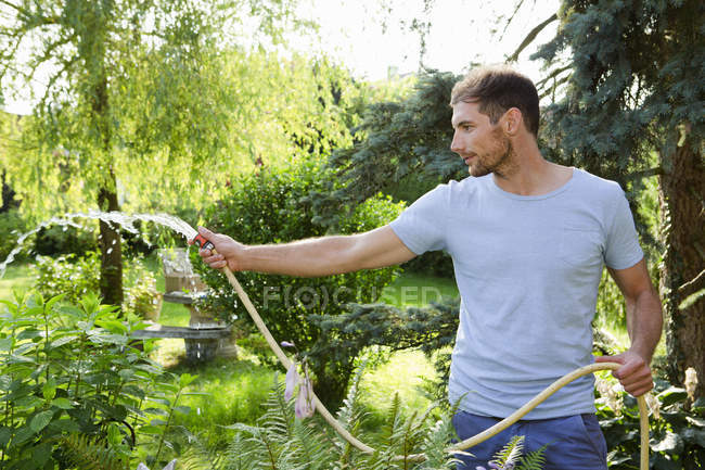 Mid adult man watering garden with hosepipe — Stock Photo